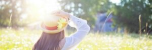 Sun Protection - Woman with hat in grass